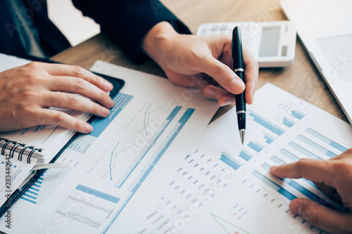 Obraz The accounting staff of the company are jointly analyzing the graph of the expenses on the desk in the office. - fototapety do salonu