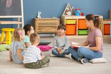 Nursery Teacher With Cute Little Children In Kindergarten