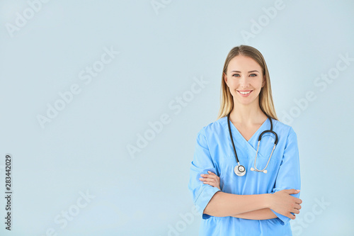 Foto  Female nurse with stethoscope on color background