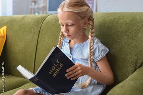 Photo Little girl reading Bible at home