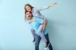 Leinwandbild Motiv Happy young couple having fun on color background