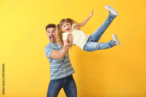 Fotomural  Happy father playing with daughter on color background