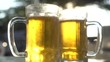 Closeup of two fresh lager beer mugs with sun rays in hot summer day