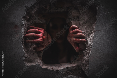 Halloween holiday, Horrible scary zombie with bloody hands is climbing in abandoned house Canvas Print