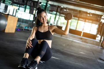 Sporty beautiful woman exercising with dumbbell weight training equipment with blurry background, Healthy life and gym exercise equipments and sports concept, with copy space