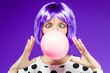 canvas print picture - Beautiful girl in violet wig is blowing a huge pink bubble with bubblegum. Stylish fashion woman dressed in blouse with polka dots. Bright young female on purple background. Fun and gladness concept.