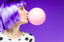 Beautiful Girl In Violet Wig Is Blowing A Huge Pink Bubble With Bubblegum. Stylish Fashion Woman Dressed In Blouse With Polka Dots. Bright Young Female On Purple Background. Fun And Gladness Concept.
