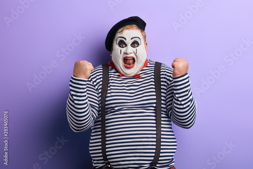 Fotografie, Obraz  carzy fat mime with raised arms rejoicing at success, victory, isolated blue background, studio shot