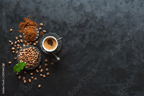 Door stickers Cafe Cup of coffee and coffee beans with ground powder on black background, top view