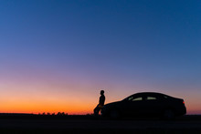 Silhouette Of A Man And A Car On A Background Of A Very Beautiful Sunset. Freedom And Travel By Car Concept.