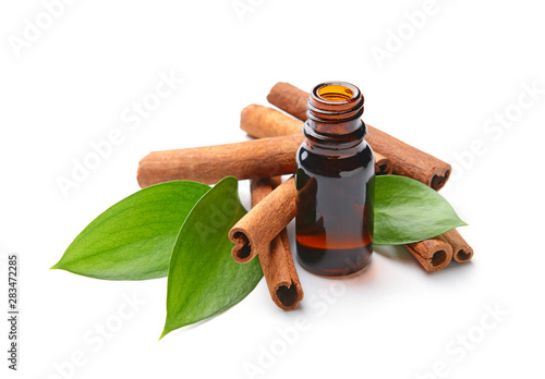 Fototapeta Aromatic cinnamon sticks and essential oil on white background obraz