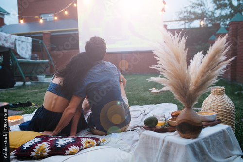 Couple in love watching a movie, in twilight, outside on the lawn in a courtyard Fotobehang