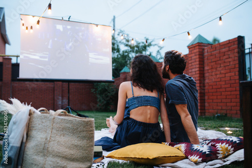 Fotografia Couple in love watching a movie, in twilight, outside on the lawn in a courtyard