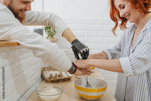 Fotografia  A young man with artificial limb are cooking in the kitchen with his girlfriend