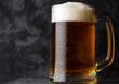 A mug of light beer on a dark concrete background