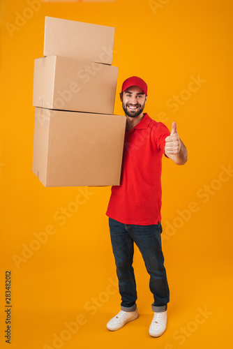 Obraz Full length portrait of handsome delivery man in red uniform showing thumb up while carrying packaging boxes - fototapety do salonu