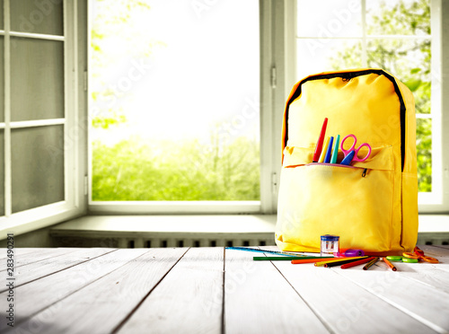 Spoed Foto op Canvas Londen Table background and a schoolbag with some colorful school supplies. Empty space for advertising products and decoration.