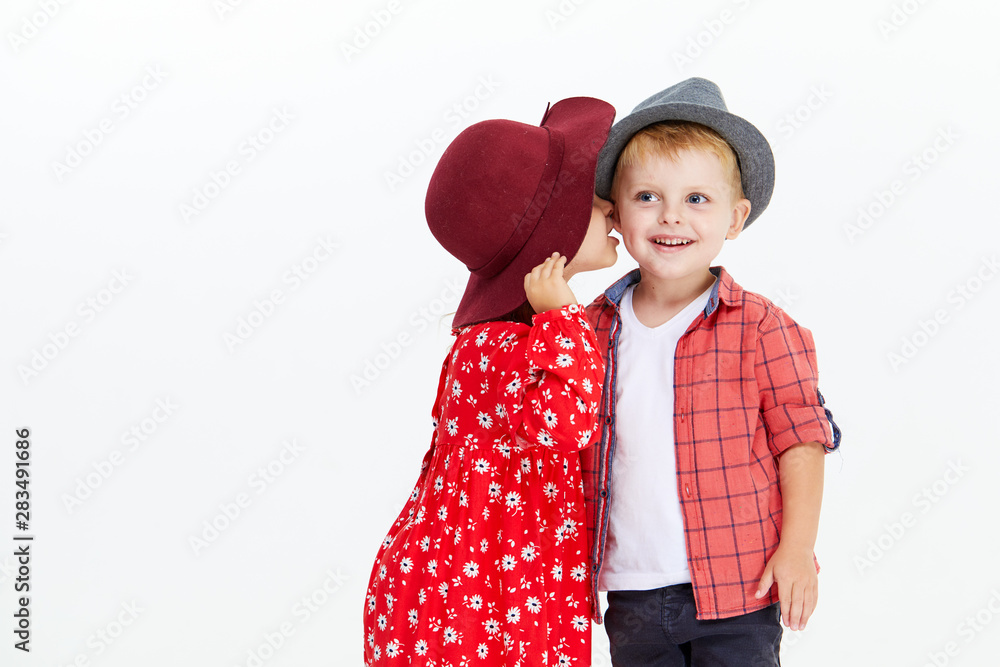 Fototapeta Happy brother and sister in hats embracing each other. Little toddler girl whispers in the boy's ear and hugs him on white background. Autumn clothes