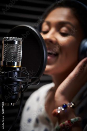 Obraz na plátně Female Vocalist Wearing Headphones Singing Into Microphone In Recording Studio