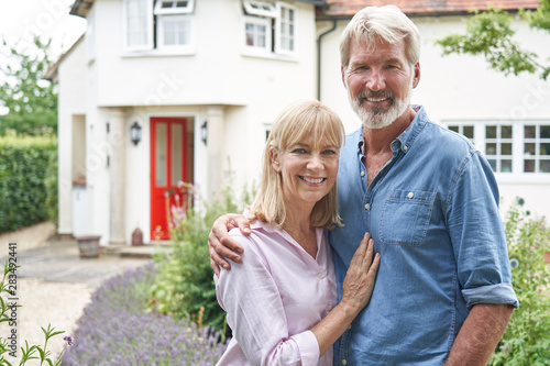 Photo Portrait Of Mature Couple Standing In Garden In Front Of Dream Home In Countrysi
