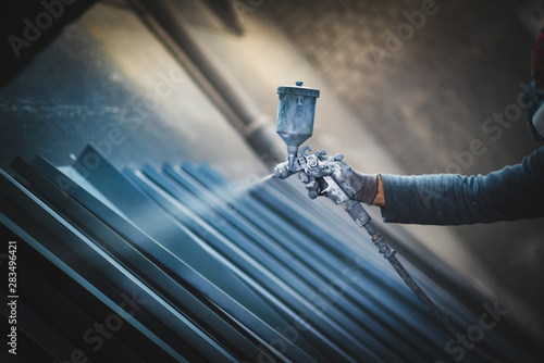 Fotografie, Obraz  Man painting metal products with a spray gun