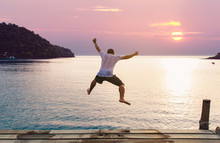 Young Man Jumping Into The Sea From Wooden Jetty On A Beach. Happy Summer Vacation Concept.