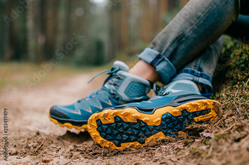 Canvas Print Male legs wearing sportive hiking shoes outdoor