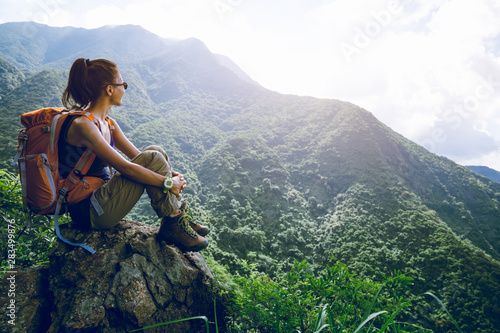 Fototapeta Young woman backpacker enjoy the view at mountain peak obraz