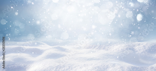 Obraz Winter snow background with snowdrifts, with beautiful light and snow flakes on the blue sky, beautiful bokeh circles, banner format, copy space. - fototapety do salonu