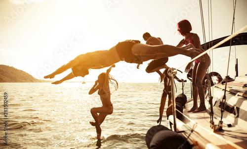 grupa przyjaciół nurkujących w wodzie podczas wycieczki łodzią