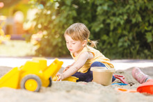 Little Girl Having Lots Of Fun With Her Toys Playing In The Sandbox