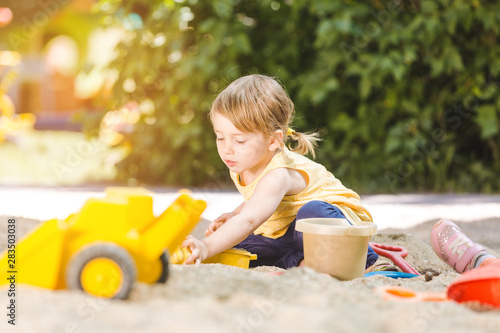 Little girl having lots of fun with her toys playing in the sandbox Canvas Print