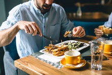 Close Up Shoot Of Man Eating In Restaurant