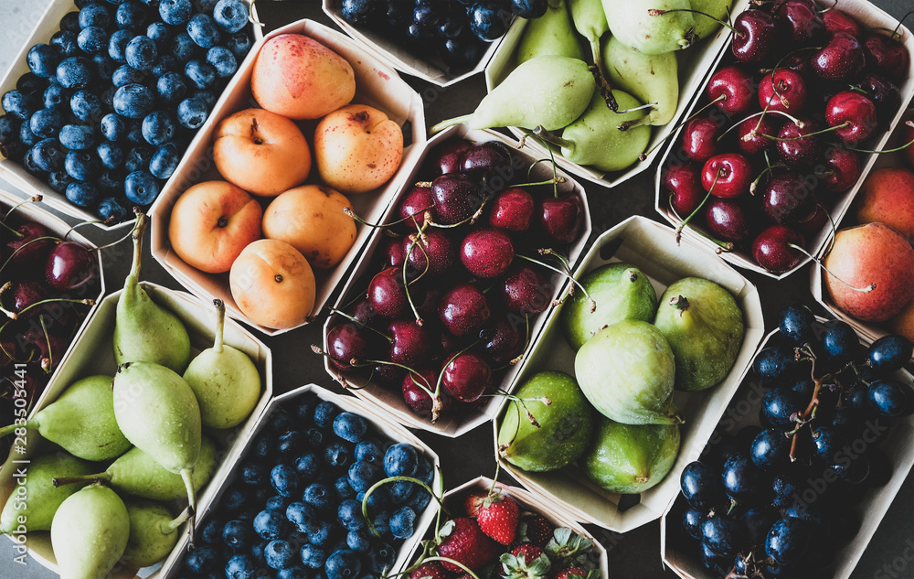 Fototapeta Summer fruit and berry variety. Flat-lay of ripe strawberries, cherries, grapes, blueberries, pears, apricots, figs in wooden eco-friendly boxes over grey background, top view. Local farmers produce