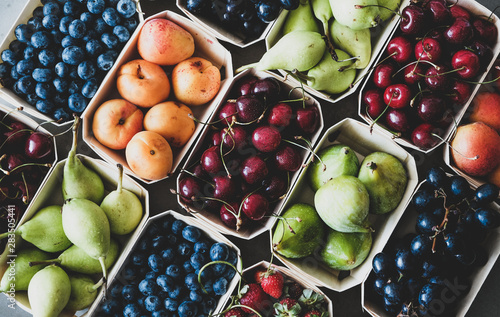 Summer fruit and berry variety. Flat-lay of ripe strawberries, cherries, grapes, blueberries, pears, apricots, figs in wooden eco-friendly boxes over grey background, top view. Local farmers produce - 283505441