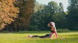 Young sporty girl training in morning sunny park. Woman doing yoga in the park. Athlete woman doing stretching exercise in summer park. Healthy sports lifestyle.