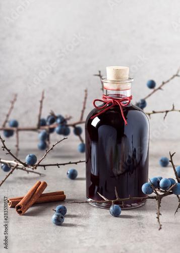 Valokuva  Bottle of homemade sweet sloe liqueur with cinnamon