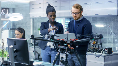 Obraz Caucasian Male and Black Female Engineers Working on a Drone Project with Help of Laptop and Taking Notes. He Works in a Bright Modern High-Tech Laboratory. - fototapety do salonu