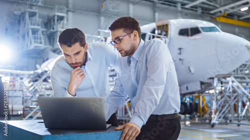 Fotomural  Two Aircraft Mechanics Working and Having Conversation next to Laptop Computer
