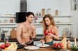 sexy couple standing near table with food and holding wine glasses