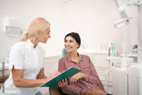 Valokuva  Woman sharing her information with the dentist.