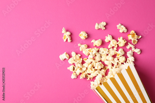 Flat lay composition with striped box and popcorn on color background - 283529033
