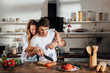 happy couple smiling while cooking together in kitchen
