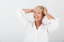 Portrait Of Joyous Adult Woman With Short Blond Hair Grabbing Her Head And Laughing At Camera