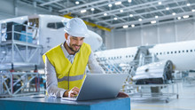 Engineer In Safety Vest Working On Computer In Aircraft Maintenance Hangar