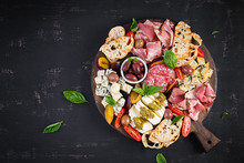 Antipasto Platter With Ham, Prosciutto, Salami, Blue Cheese, Mozzarella With Pesto And Olives On A Wooden Background. Top View, Overhead