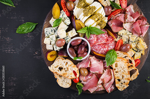 Fényképezés Antipasto platter with ham, prosciutto, salami, blue cheese, mozzarella with pesto and olives on a wooden background