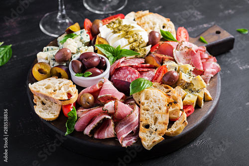 Photo Antipasto platter with ham, prosciutto, salami, blue cheese, mozzarella with pesto and olives on a wooden background