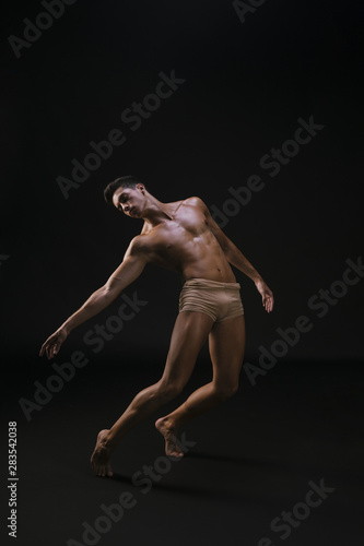 Fotomural  Naked athletic man standing and extending hand