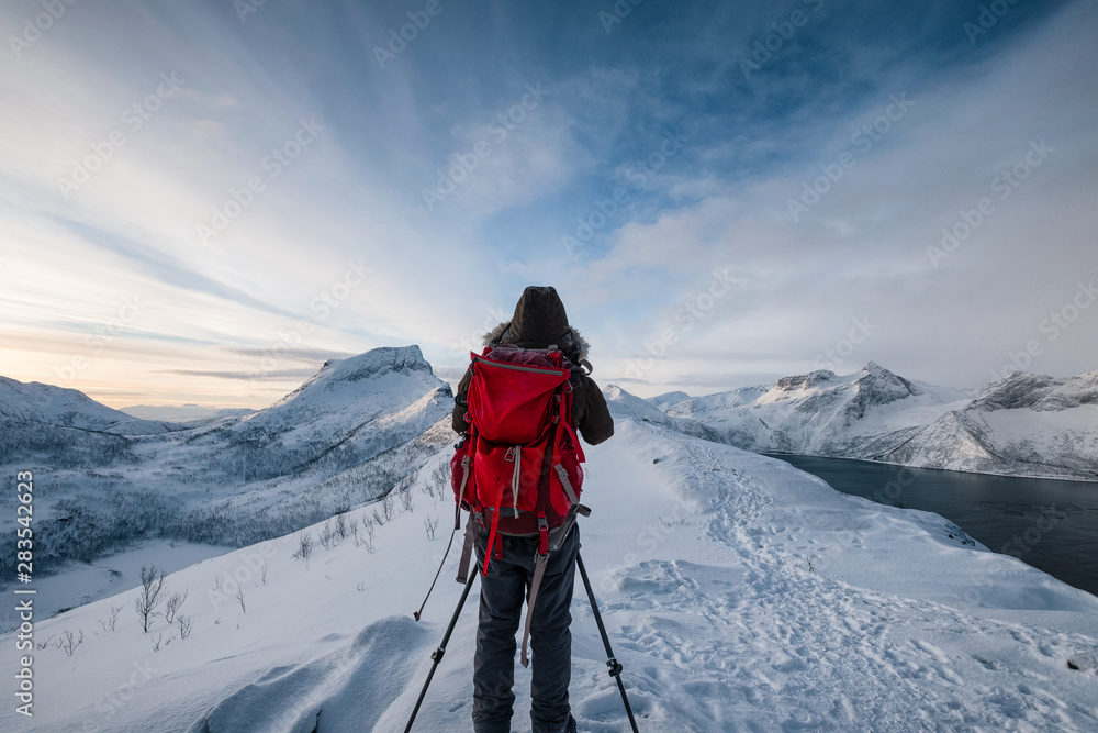 Fototapety, obrazy: Mountaineer with backpack taking a photo a scenery on mountain peak